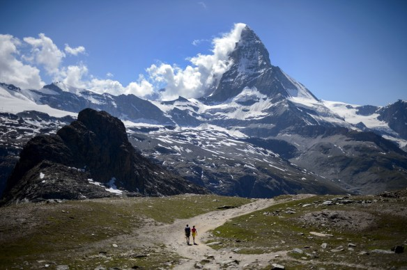 A couple of tourists walk on a trail below the Matterhorn mountain in Zermatt on June 30, 2015. The resort celebrates this year the 150th anniversary of the iconic Alpine mountain's first climb. AFP PHOTO / FABRICE COFFRINI (Photo credit should read FABRICE COFFRINI/AFP/Getty Images)